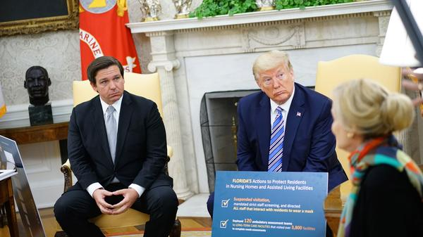 Gov. Ron DeSantis, pictured during a meeting with President Trump on Tuesday, has announced plans to reopen businesses in Florida.