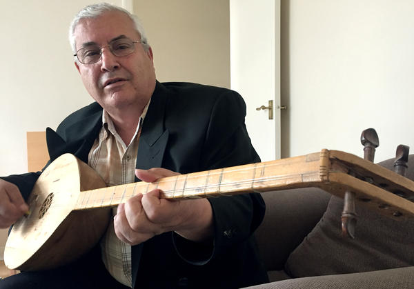 """Khoshaba Jaber, an Assyrian living in West London, plays a tambura, a traditional instrument known as the """"mother of strings,"""" after singing an epic poem he learned in his boyhood village in northern Iraq."""