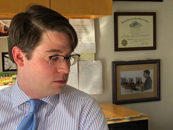 Institute for Justice lawyer Wesley Hottot in his Seattle office. On the wall is a framed illustration of him arguing <em>Timbs v. Indiana</em> at the Supreme Court last fall.