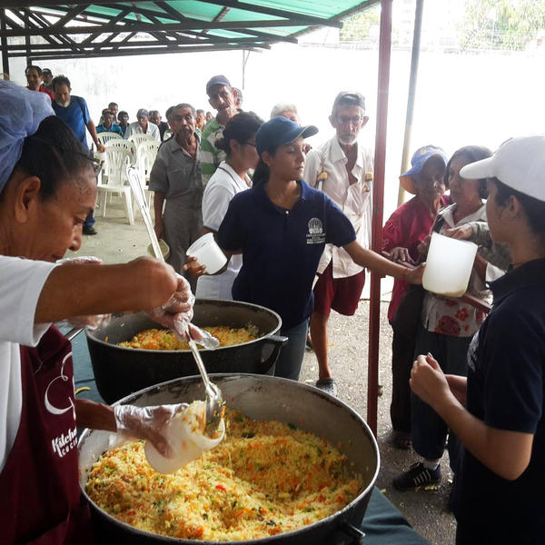 Men, women and children line up for free lunch at a soup kitchen in Maracaibo, Venezuela. The meal consists of a bottle of milk and a few scoops of rice mixed with eggs and vegetables.