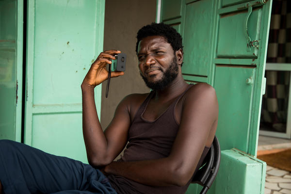 Abdoulie Nyang listens to the hearings of the truth commission on the small black radio in his palm.
