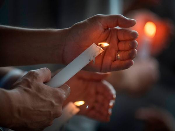 People light candles during a prayer and candle vigil organized by the city, after the recent shooting at a WalMart in El Paso, Texas.