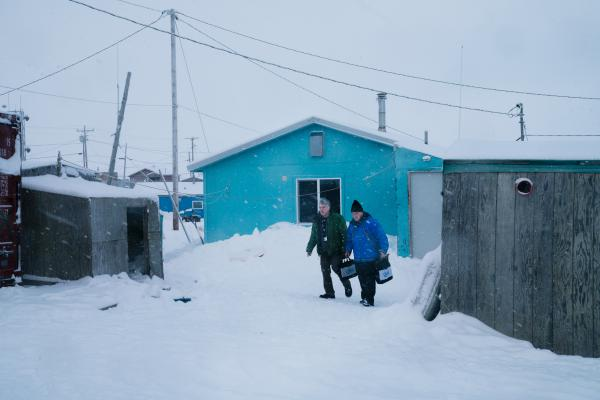 Steven Dillingham (right), the Census Bureau's director, walks through Toksook Bay, Alaska, on Tuesday and went to count the first person for the census.