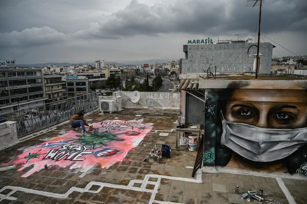 Street artist S.F. paints a mural about the COVID-19 crisis on the roof of his building in Athens, Greece, on Monday.