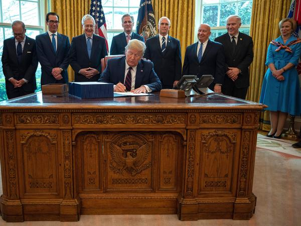 President Trump signs the CARES act, a $2 trillion rescue package to provide economic relief amid the coronavirus outbreak, at the Oval Office of the White House on Friday.