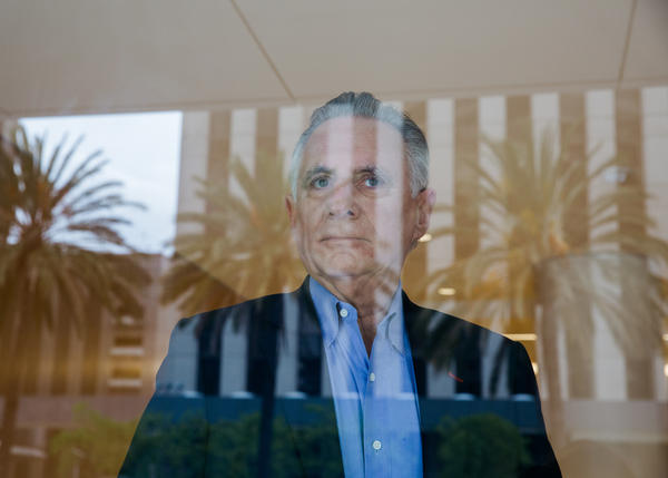 Co-founder Martin Pichinson stands behind a window at Sherwood Partners, which helps shut down startups in financial trouble.
