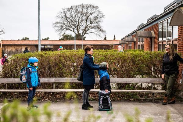 Parents and their children stand in line waiting to get inside Stengaard School north of Copenhagen, Denmark.