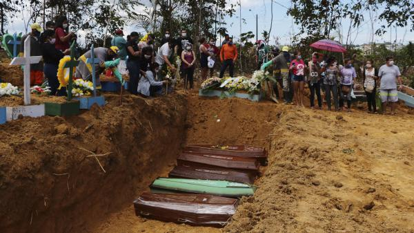 Relatives mourn at the site of a mass burial at the Nossa Senhora Aparecida cemetery, in Manaus, Amazonas state, Brazil, on Tuesday. The cemetery is carrying out burials in common graves due to the large number of deaths from COVID-19 disease, according to a cemetery official.