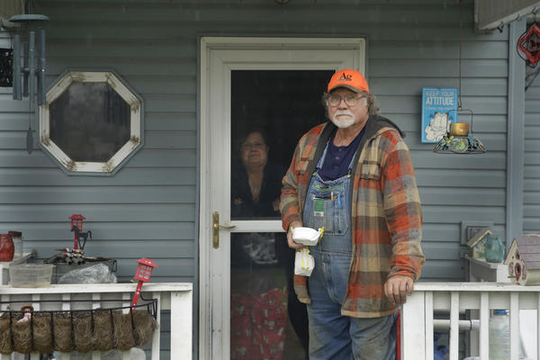 Dennis Ruhnke holds two of his remaining N-95 masks as he stands with his wife, Sharon, at their home near Troy, Kansas, on April 24.