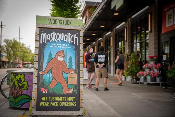 <p>A sign at the Woodstock location of New Seasons Market in Portland, Ore., alerts customers that they must wear face masks while shopping on Wednesday, April 29, 2020.</p>