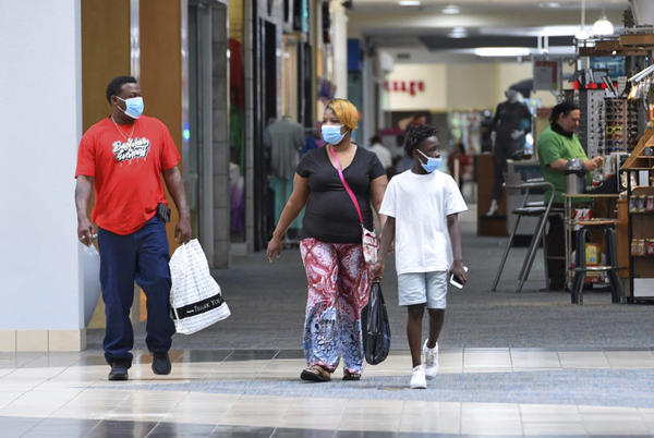 Ronnie Johnson, left, Gwen Evans, center, and Jamarion Davis shop while wearing masks to protect against coronavirus,  after the Anderson Mall opened to limited business, Friday, April 24 2020 in Anderson, S.C. (Richard Shiro/AP Photo)
