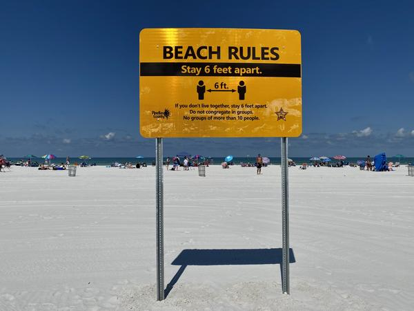 Clearwater Beach opened to the public on Monday with signs warning beachgoers to practice social distancing.