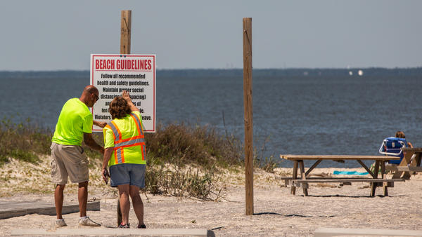 """Public workers install a """"Beach Guidelines"""" sign displaying new social distancing rules at a public beach in Dauphin Island, Ala., on Friday. Alabama has reopened some businesses, with restrictions."""