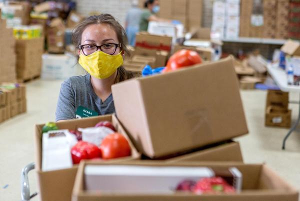 A volunteer prepares boxes of food at the Kelly Memorial Food Pantry in Central El Paso, which has served 700 to 1,000 families a day during the COVID-19 pandemic.