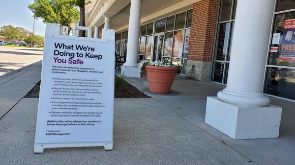 Signs greet shoppers at the St. Johns Town Center, encouraging them to keep socially distant.
