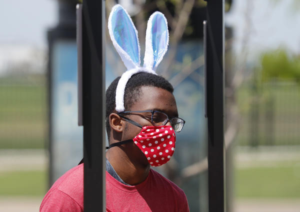 Amid COVID-19 concerns, a fast food worker wears a mask and Easter bunny ears as he works at a Chick-fil-A restaurant in Dallas on Tuesday.