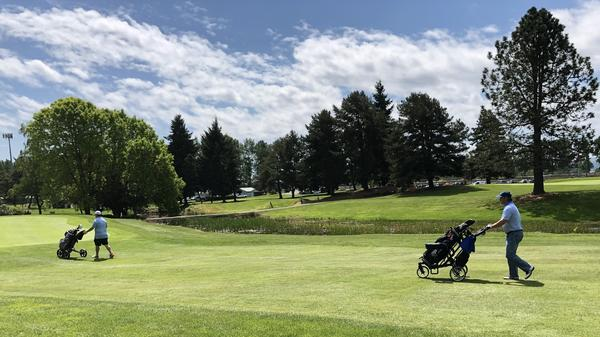 Curt Fitzpatrick (left) and Ross Jepson keep their distance on Three Rivers Golf Course in Kelso, Wash. The state lifted COVID-19 restrictions on golf courses after a month-and-a-half shutdown.