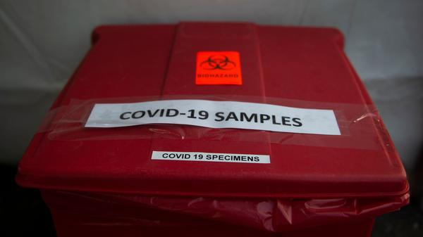 A bucket used to collect samples after people have been tested for COVID-19 is seen at a drive through testing site in Arlington, Va., on March 20. One group in northern Virginia is paying special attention to the coronavirus's impact on Latinos.