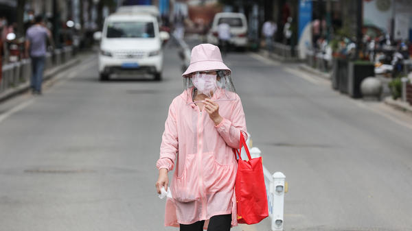 A woman wears a face mask on Monday as she walks along a street in Wuhan, in China's central Hubei province. Wuhan reported new cases of COVID-19 after going more than a month without new infections.