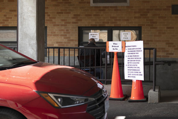 A congregant pulls up a chair to the drive-thru confessional at St. Francis of Assisi Monday morning. Father Anthony Yates and George Staley take turns manning the window three days a week, to provide spiritual solace for parishioners during the pandemic.