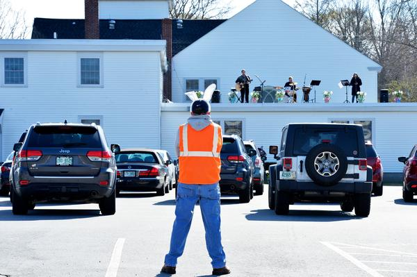 Volunteer Al Wheeler, wearing bunny ears, keeps an eye on the service and cars during a drive-in Easter service at First Baptist Church in Plaistow, N.H., on April 12. Since the COVID-19 pandemic has made services inside the church a danger to health, the church started holding gatherings in its parking lot.