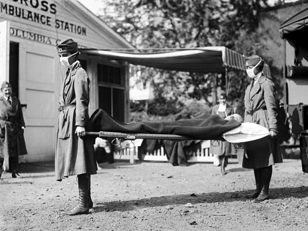 Two Red Cross nurses carry a person on a stretcher during a demonstration at the Red Cross Emergency Ambulance Station in Washington, D.C., in 1918.