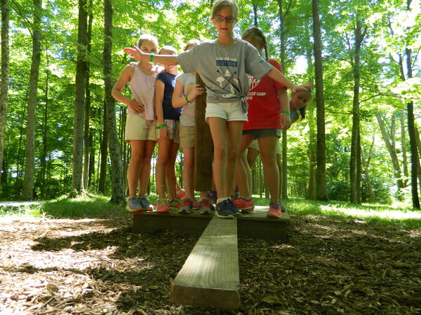 Campers work together on the low ropes course at YMCA Camp Ernst in more certain times.
