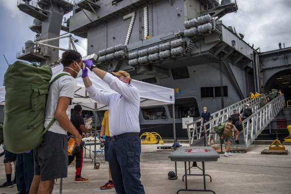 Sailors have their temperatures taken as they prepare to board the USS Theodore Roosevelt May 1, 2020 after an off-ship quarantine in Guam.