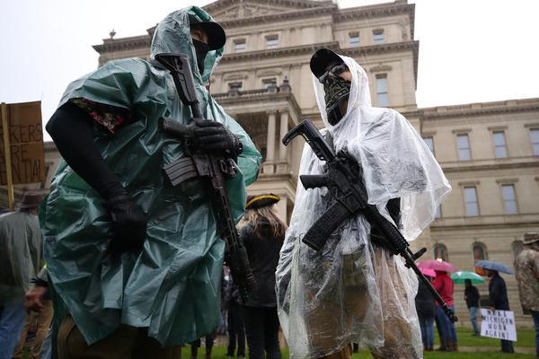 Protesters carrying weapons gather at the Michigan Capitol on Thursday in Lansing. Protesters are demonstrating against Democratic Gov. Gretchen Whitmer for the coronavirus stay-at-home order in effect through May 28.
