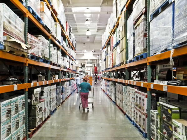 Shoppers walk the aisles of Costco. A small business owner in the remote town of Gustavus, Alaska, travels 14 hours to reach Juneau, where he shops for critical supplies to stock his store shelves.