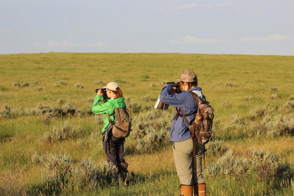 Kayla Ruth and Samantha Bundick look through binoculars in 2016 while doing research aimed at determining the species of songbirds they're observing on private lands in Eastern Montana.