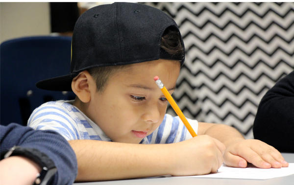 A first-grader practices spelling at Broken Arrow Elementary during a small-group phonics lesson in 2018.