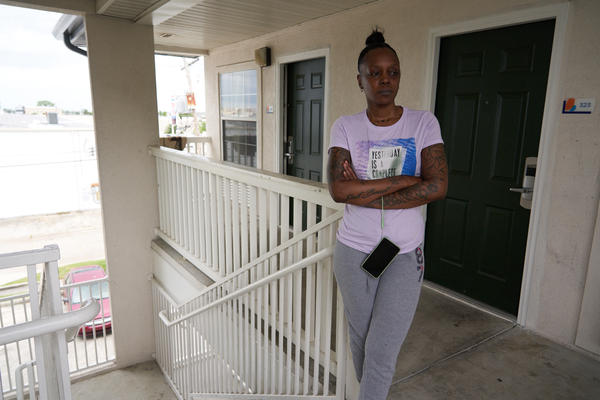 "Jaronda Hinton in front of her room at the InTown Suites Extended Stay. Hinton has livied in the hotel for a month with her teen children. Hinton says, ""I'm out of funds, I was paying $295 a week. Police put two people out today."" April 7, 2020."