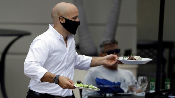 A food server wears a protective face mask as he delivers food to customers at the Parkshore Grill restaurant Monday, May 4, 2020, in St. Petersburg, Fla.