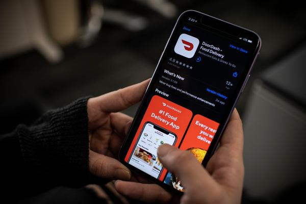 An AFP journalist checks the DoorDash food delivery application on her smartphone in Washington, DC.