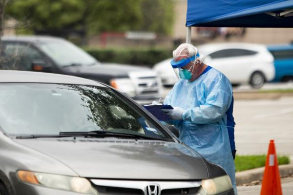A man in protective gear takes down information from a driver at a drive-thru coronavirus testing site.