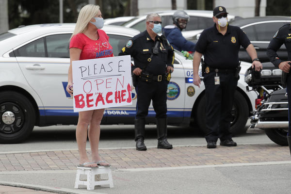 """A protestor, who did not want to be identified, holds a sign reading """"Please Open Beaches"""" as Florida Gov. Ron DeSantis speaks at a news conference during the new coronavirus pandemic, Thursday, May 14, 2020, in Doral, Fla. DeSantis has signed an executive order for the gradual reopening of Miami-Dade and Broward counties on May 18. (AP Photo/Lynne Sladky)"""