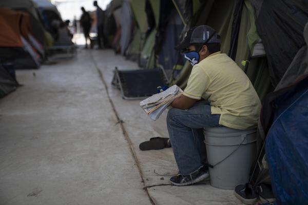 Honduran asylum seeker Malek Gaitan, 8, studies words in English at the migrant camp where he lives in Matamoros.