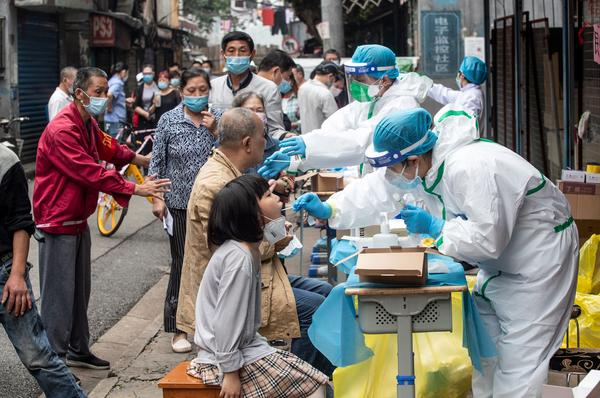 Medical workers take swab samples from residents to be tested for the COVID-19 coronavirus, in a street in Wuhan in China's central Hubei province on May 15, 2020.  (STR/AFP via Getty Images)