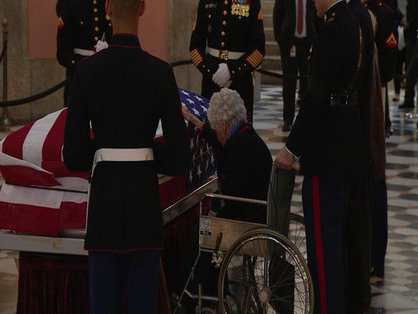 Annie Glenn touches her husband's casket as he lies in state in the Rotunda of the Ohio Statehouse on December 16, 2016.