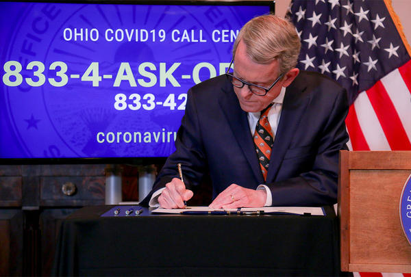 Gov. Mike DeWine signs an executive order.