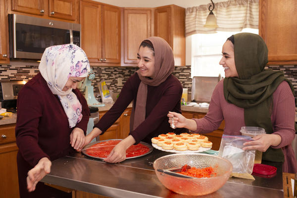 From left, Huda Attar and her daughters, Eslah and Shorook, in the kitchen baking. Huda is teaching Eslah how to make <em>knafeh</em>, a Middle Eastern dessert consisting of a thin noodle pastry stuffed with cheese, soaked in syrup and topped with pistachios.