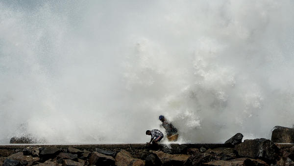 Two men duck for cover as waves generated by Cyclone Amphan smash against a breakwater Tuesday in Chennai, India. Farther north along India's east coast, near the country's border with Bangladesh, officials are struggling to evacuate areas in the storm's path.