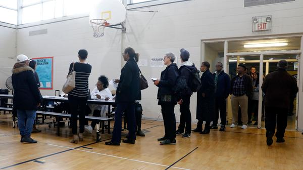People stand in line at a Detroit polling place during Michigan's March 10 presidential primary. As a result of the pandemic, the state's top election official is sending absentee ballot applications to every registered voter for August and November elections.