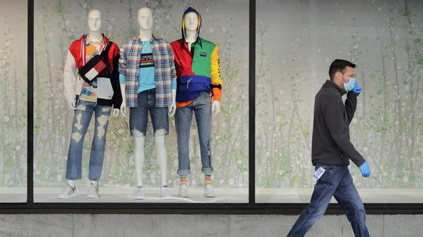 "A man walks past mannequins in the windows of a Macy's store in Boston on April 15. The company said its online sales started growing in April, but they ""only partially offset"" the losses from its stores."