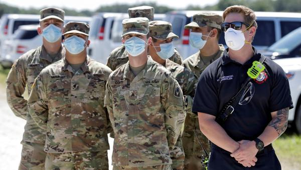 A Sarasota County paramedic, right, stands with members of the Florida National Guard wearing protective face masks during a coronavirus news conference with Gov. Ron DeSantis Tuesday, May 5, 2020.