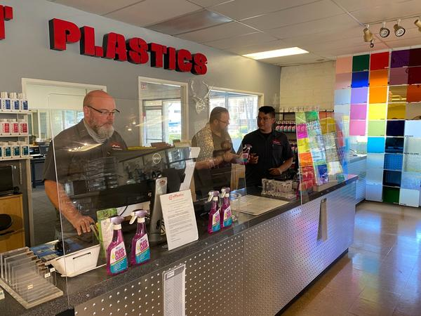 """John Short (middle) of ePlastics in San Diego stands with employees behind their """"sneeze guards."""" (Courtesy)"""