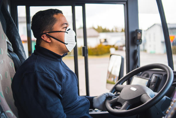Busdriver with mask puts protecting gloves on his hands to protect himself from the coronavirus epidemic.