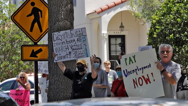 Protestors wave signs at Florida Gov. Ron DeSantis as he and Vice President Mike Pence visit the Westminster Baldwin Park Wednesday, May 20, 2020, in Orlando, Fla.