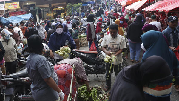 People shop in preparation for the Eid al-Fitr holiday at a market in Jakarta on Friday.